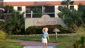 a toddler at the sandalfoot sign