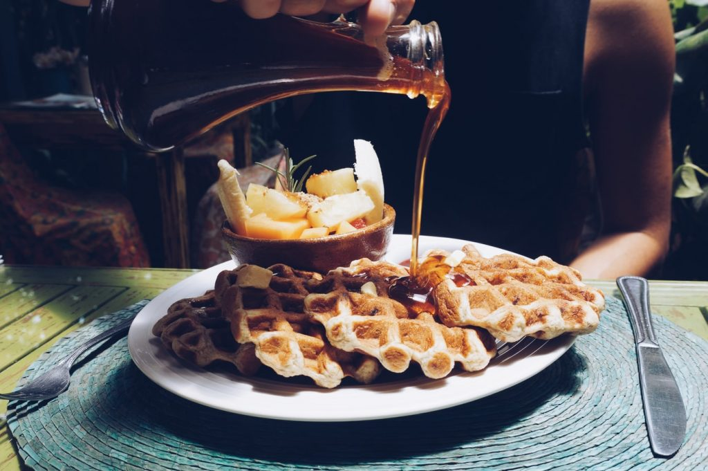 pouring syrup over waffles
