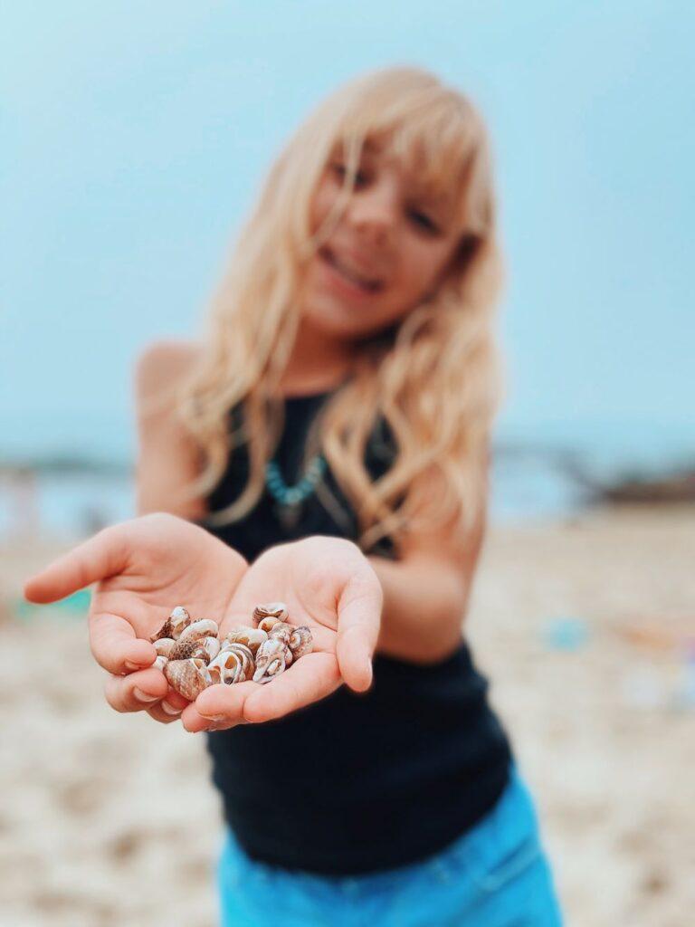 girl holding shells in her hand