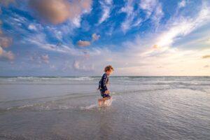 boy running through surf